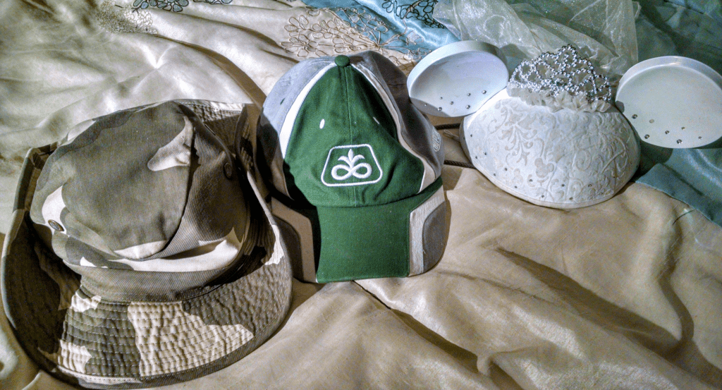 From left to right: Fake military boonie hat that I bought on the beach in San Diego, a baseball cap that a reader gave me and... crap, you weren't supposed to see that one. Move along now.